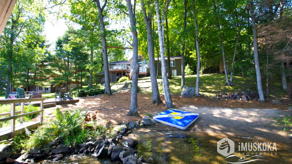 Natural Landscaping beautiful trees, level lot and sand beach.